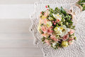 Beautiful wedding bouquet of roses and freesia with lace on white wooden background, background for valentines or wedding day Royalty Free Stock Photo