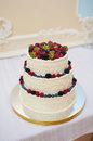 Beautiful wedding cake with berries on wooden table Royalty Free Stock Photo