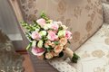 Beautiful wedding colorful nosegay on chair of pink and peach roses Royalty Free Stock Photos