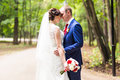 Beautiful wedding couple in park. They kiss and hug each other Royalty Free Stock Photo