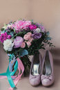 Beautiful wedding shoes with high heels and a bouquet of colorful flowers
