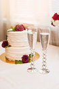 Beautiful white cake with red roses and two glasses with champagne Royalty Free Stock Photo