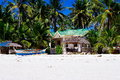 Beautiful white coral sand beach with palms and cottages, turquoise blue ocean Royalty Free Stock Photo