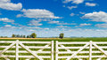 Beautiful white picket fence door a gate in front of a farmland on a sunny day Royalty Free Stock Images