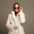 Beautiful winter girl in white fur and sunglasses. winter fashion.young woman Royalty Free Stock Photo