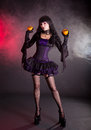 Beautiful witch in purple and black gothic halloween costume fantasy with jack lantern oranges Stock Photos