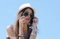 Beautiful woman against blue sky with long brunette hair wearing hat and sunglasses as background horizontal photo Royalty Free Stock Photo