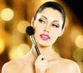 Beautiful woman applying blusher on face portrait of using cosmetic brush Royalty Free Stock Photo