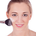 Beautiful woman applying make up on face Stock Photo