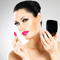 Beautiful woman applying pink lipstick on lips makes makeup Stock Images
