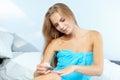 Beautiful woman applying red nail polish in bed at home Royalty Free Stock Photo
