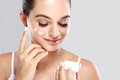 Beautiful woman applying some cream to her face portrait of for skin care Royalty Free Stock Image