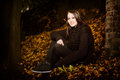 Beautiful woman in autumn leaves sitting outside the darkness on the ground alongside a brick wall with copyspace Royalty Free Stock Photography