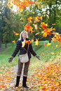 The beautiful woman in autumn park throws up red maple leaves in a sunny day Stock Images