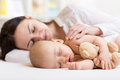 Beautiful woman and baby sleeping together in a women her son little bedroom Royalty Free Stock Image