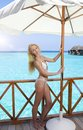 Beautiful woman in bathing suit under a sun protection umbrella on a wooden terrace and the sea on a background, Maldives Royalty Free Stock Photo