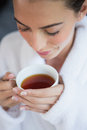 Beautiful woman in bathrobe having tea close up of a young Stock Images