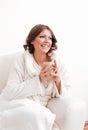 Beautiful woman in bathrobe holding a mug smiling Stock Image