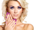 Beautiful woman with beauty purple manicure and makeup of eyes blond fashion model curly hairstyle Royalty Free Stock Photo