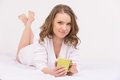 Beautiful woman in bed drinking tea smiling coffee lying on at home Royalty Free Stock Photography