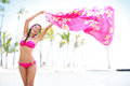 Beautiful woman in bikini on beach waving scarf pink happy bliss travel vacation graceful pretty mixed race young pink Royalty Free Stock Image