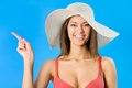 Beautiful woman in bikini and hat pointing on a blue background Royalty Free Stock Photo