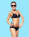 Beautiful woman in bikini portrait of young black and sun glasses on blue Royalty Free Stock Photography