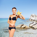 Beautiful woman in bikini on sea background portrait of young black posing with star Stock Photo