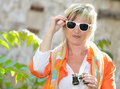 Beautiful woman with binoculars and sun glasses blond colored scarf holding binocular Royalty Free Stock Photo