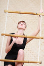 Beautiful woman in black climbs at bamboo rope ladder Royalty Free Stock Images