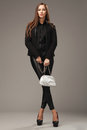 Beautiful woman in black clothing with a silver fashion bag Royalty Free Stock Photo