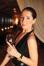 Beautiful woman black dress glass wine dark background vertical frame Stock Photo