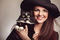 Beautiful woman in black dress and hat with cat Royalty Free Stock Photo