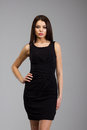 Beautiful woman in a black dress standing over gray background Stock Photo