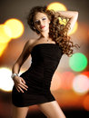 Beautiful woman in black dress young poses over night lights Stock Photography