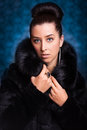 Beautiful woman in black fur coat on the blue luxury Stock Photography