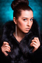 Beautiful woman in black fur coat on the blue luxury Stock Photos