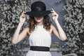 Beautiful woman in a black hat and a white dress on background o Royalty Free Stock Photo