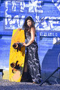 Beautiful woman in black white dress, long hair  standing with wakeboad on the bacground blue iron, graffiti