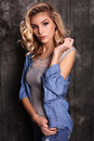 Beautiful woman with blond curly hair and evening makeup,wears jeans clothes Royalty Free Stock Photo