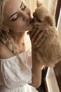 Beautiful woman with blond hair with cute little dog portrait of girl in elegant white dress posing beside a window small Royalty Free Stock Image