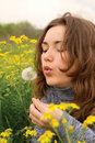 Beautiful woman blowing dandelion seeds Royalty Free Stock Images