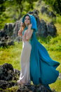 Beautiful woman with blue cloak posing outdoor Stock Photography