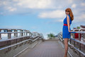Beautiful woman in blue dress and red belt standing on the bridge Stock Photography