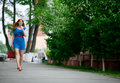 Beautiful woman in blue dress and red shoes outdoors ginger haired walking Royalty Free Stock Photography