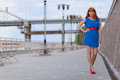 Beautiful woman in blue dress and red shoes sexy walking near bridge Royalty Free Stock Images