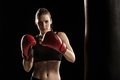 Beautiful woman is boxing on black background Royalty Free Stock Photo