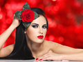 Beautiful woman with bright fashion makeup holds red rose portrait of the attractive model posing over background Stock Photo