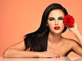 Beautiful woman with bright fashion makeup portrait of the pretty holds red rose attractive model posing at studio Royalty Free Stock Photo
