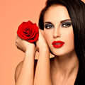 Beautiful woman with bright fashion makeup portrait of the pretty holds red rose attractive model posing at studio Stock Image